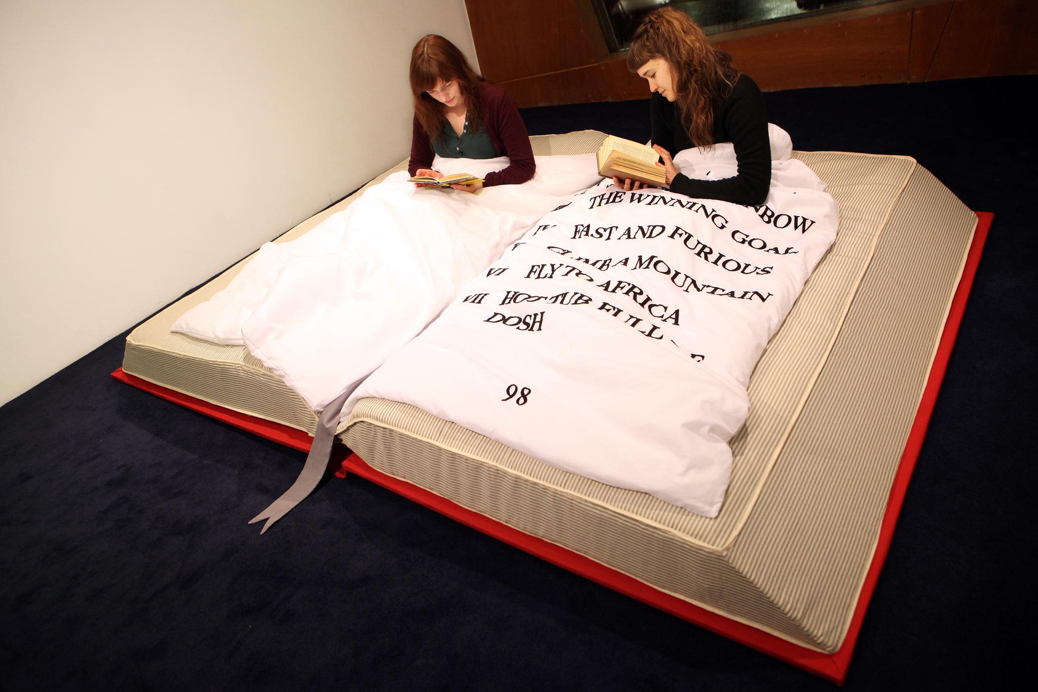 desain-tempat-tidur-berbentuk-buku-terbuka-dengan-selimut-bertulisan